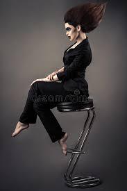 si e de bar donna alla moda di affari che si siede sullo sgabello da bar