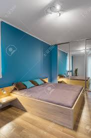 geräumiges schlafzimmer in weiß und blau mit großem bett und spiegelschrank