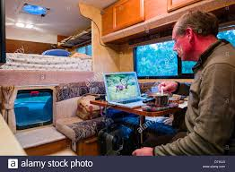 Professional Photographer Editing Digital Photographs On Laptop Computer Inside A Camper Truck Denali National