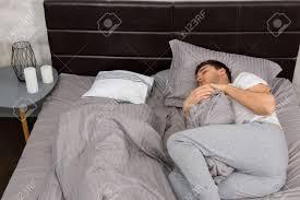 gut aussehend müde mann im pyjama allein ohne decke schlafen und ein kissen in den stilvollen bett in grauen farben und in der nähe nachttisch mit
