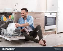 Happy Handsome Man Unloading Dishwasher And Enjoying In Housework Husband Doing Chores Kitchen