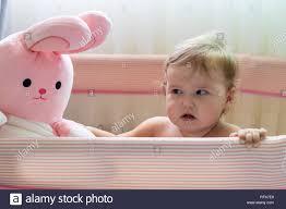 lachendes baby stehen in einem rosa bett rosa