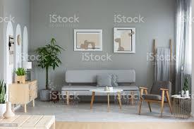 zwei plakate aufhängen an der wand in echtes foto grauen wohnzimmer interieur mit frischpflanzen mit kissen und couchtisch aus holz