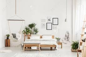 holzbank und king size bett im geräumigen weißen schlafzimmer interieur mit pflanzen zeichnung und hängematte