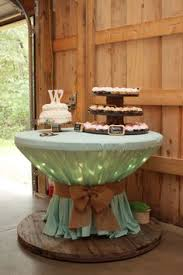 Wooden Spool With Icicle Lights Covered Round Table Cloth Used A Bungee Cord To Rustic Wedding DecorationsRound