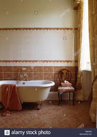 roll top bad in terracotta und weiß gefliestes badezimmer