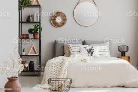 runder spiegel und hölzerne uhr an der wand des eleganten schlafzimmer mit beige bettwäsche und weiße warme decke echtes foto stockfoto und mehr