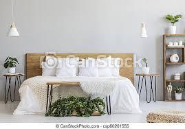 len über holzbett mit weißen laken in grauem schlafzimmer