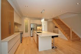 Clear Maple Wood Flooring With A White Kitchen