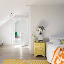 Create A Year Round Holiday Feel Escape To This Attic Bedroom With Its Zingy Palette Of Tropical Colours The Bold Yellow And Orange Decor Pops In An