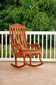 Gorgeous Simple Wooden Rocking Chair On Porch. Brown, Green,..