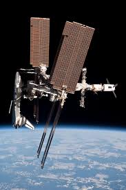 A Side On View Of The ISS Showing Space Shuttle Docked To Forward