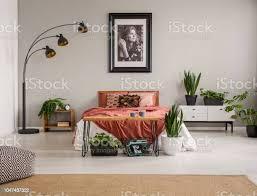 hocker auf teppich und pflanzen vor roten bett in grau schlafzimmer innenraum mit poster und le echtes foto stockfoto und mehr bilder bett