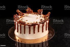 runde weiße torte mit karamell und schokolade puffreis auf ein rundes tablett auf schwarzem hintergrund stockfoto und mehr bilder anziehen