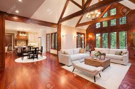 schöne und große wohnzimmer mit parkettboden hohe gewölbte decke kamin und im neuen luxus haus hat ansicht der küche