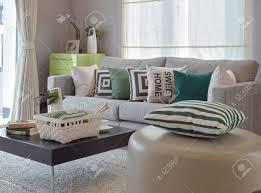 stricken im gemütlichen wohnzimmer mit grauem sofa und retro kissen gesetzt