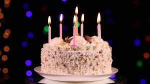 Happy Birthday cake with burning candles in front of black