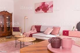 nahaufnahme zwei kaffeetassen auf dem tisch im eleganten wohnzimmer mit grau mit pastell rosa kissen stilvolle sessel und vintage schrank