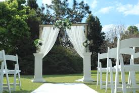 Rustic Wedding Arch With White Pedestals And Beautiful Silk Flowers In Vases