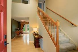 Entrance Hallway In Ivory Tones With View Of Staircase And Dining Table Set Has Light