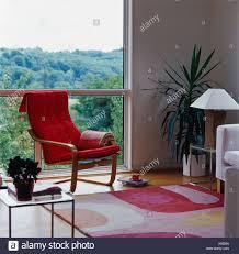 modernen wohnzimmer mit roten stuhl vor große fenster mit
