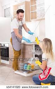 Young Happy Couple Unloading Dishwasher With Clean Crockery Working Together And Helping Each Other In Housework