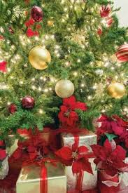 Christmas Tree Decoration With Lights Ornaments Ribbons Poinsettia And Presents Under The Stock Photo