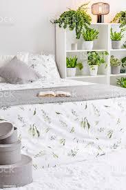 feminine schlafzimmer innenraum in weiß grau und grün mit pflanzen neben einem bett gekleidet in kissen bettdecke und decke aus natürlichen stoff