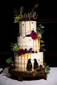 A Rustic Semi Naked Three Tier Wedding Cake Styled With Dark Purple Flowers And Foliage