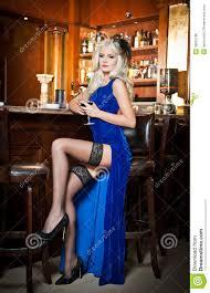 si e de bar donna bionda attraente in vestito lungo elegante che si siede