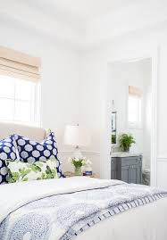 White Bedroom With Blue Patterned Pillows And Duvet Rattan Roman Shades