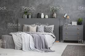 graue und weiße schlafzimmer innenraum mit einem großen bett mit bettwäsche decken und kissen schubladenschrank neben echtes foto stockfoto und mehr