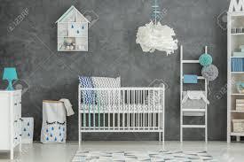 graues baby schlafzimmer mit weißem kinderbett und kommode