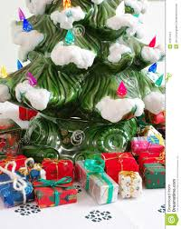 An Ceramic Christmas Tree With Miniature Wrapped Gift Packages At Its Base
