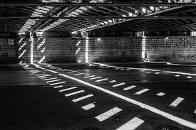 Black And White Shot Of Person Walking In Underpass With Light Shadow Pattern On Floor