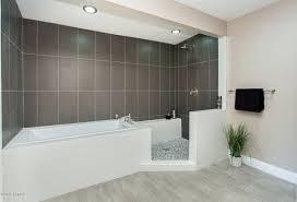 contemporary master bathroom with drop in bathtub specialty tile