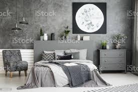 mondkunstdekor an der wand in einem eleganten grauen schlafzimmer interieur mit einem großen bett in der mitte und einen sessel und schublade schrank
