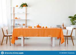 stühle bei tisch mit orange stoff im weißen