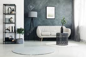 schwarzes metallgestell mit büchern vasen und dekorationen die im wohnzimmer mit pflanzen teppichen und plakat stehen