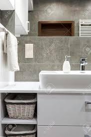 weiße möbel und graue fliesen im modernen badezimmer