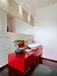 moderne rote möbel für waschbecken und holzboden im badezimmer