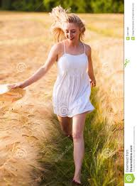 happy young blonde in white dress with straw hat running th