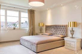 spacious bedroom in beige with big upholstered bed