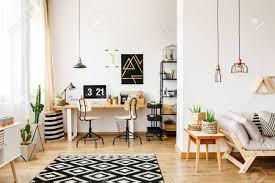 modernes zimmer im skandinavischen stil mit büro interieur mit schreibtisch poster retro stühlen und kaktus und offenem wohnzimmer mit sofa und