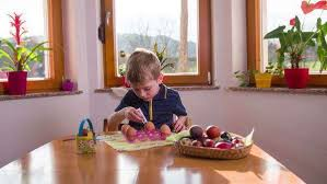 Kid Painting Egg On Big Kitchen Table Young Boy Enjoying Coloring For Easter Holiday