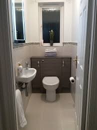 Narrow Bathroom Floor Cabinet by Small Cloakroom Grey Lined Wall And Floor Tiles Edged With Mosaic