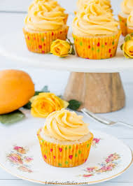 A Mango Cupcake On White Floral Plate With Stand Of Cupcakes In The Background