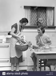 1930s 1940s TWO WOMEN AT KITCHEN TABLE WITH A BASKET OF VEGETABLES ASPARAGUS STOVE