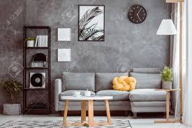 schwarze uhr und poster auf dunkler wand über grauem sofa mit gelbem kissen im gemütlichen wohnzimmer