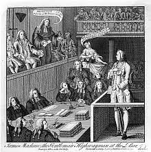 A Well Dressed Defendant Is Standing In The Dock His Legs Irons